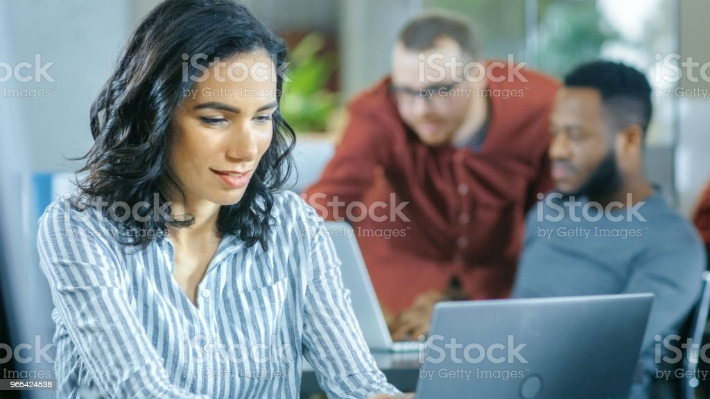 忙碌的國際辦公室, 美麗的拉美裔婦女工作在她的辦公桌上的筆記本電腦, 在背景不同的團隊創造性的同事工作。 - 免版稅一起圖庫照片