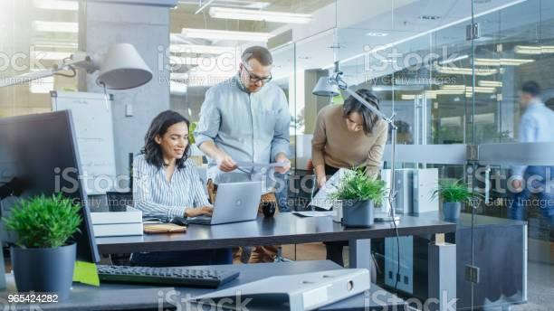 Foto de Ocupado Escritório Internacional Onde Diversas Equipe De Jovens Empresárias E Empresários Trabalham Em Laptops Ter Encontros Discussões E Desenhar Planos Em Um Quadro e mais fotos de stock de Adulto