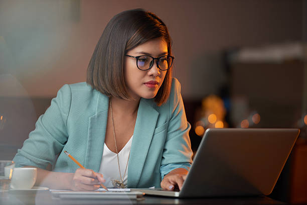 Busy lady Young Vietnamese business woman working on laptop and taking notes vietnamese ethnicity stock pictures, royalty-free photos & images