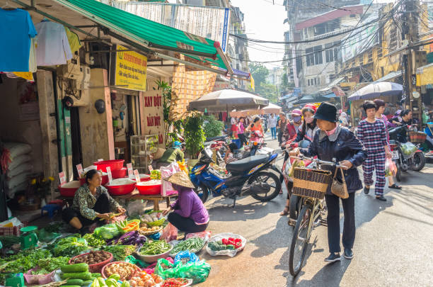 Busy local daily life of the morning street market in Hanoi, Vietnam. A busy crowd of sellers and buyers in the market. stock photo