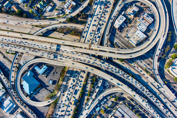 Busy Los Angeles Freeway Interchange Aerial The heavy traffic on the interchange between the Interstate 10 and 110 freeways near downtown Los Angeles, California during rush hour. multiple lane highway stock pictures, royalty-free photos & images