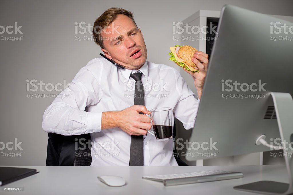 Busy man at the office having coffee and burger stock photo