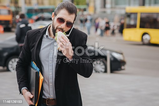 Busy man is in a hurry, he does not have time, he is going to eat snack on the go. Worker eating, drinking coffee, talking on the phone, at the same time. Businessman doing multiple tasks. Multitasking business person
