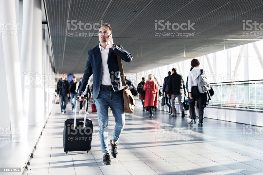 Busy man speaking on phone and walking in airport stock photo