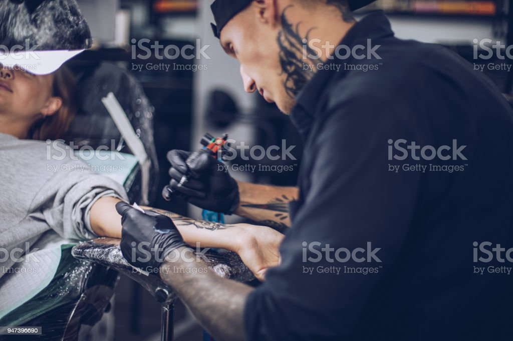 Busy man tattoo artist stock photo
