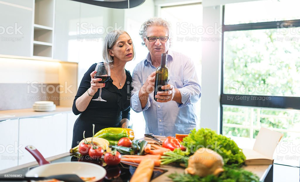 busy mature couple cooking in the kitchen stock photo