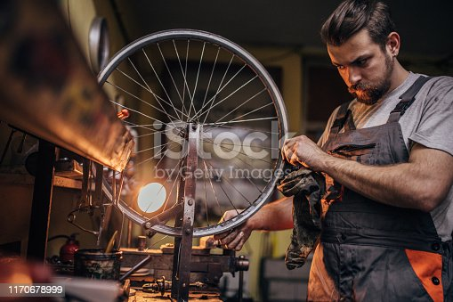 One man, bicycle mechanic repairing a bicycle in his work shop.