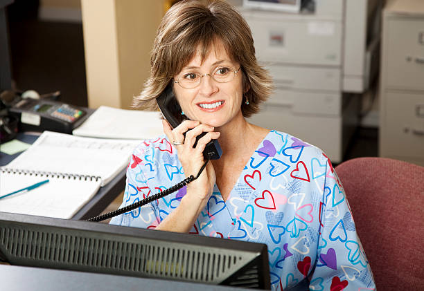 busy medical receptionist - nurse on phone stock photos and pictures