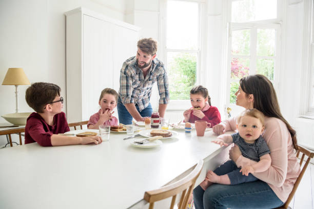 Busy modern family with two girls and two boys having breakfast at dining table stock photo