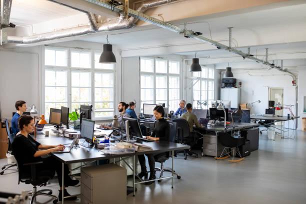 スタッフが対応する忙しいモダンなオープンプランオフィス - オフィス ストックフォトと画像