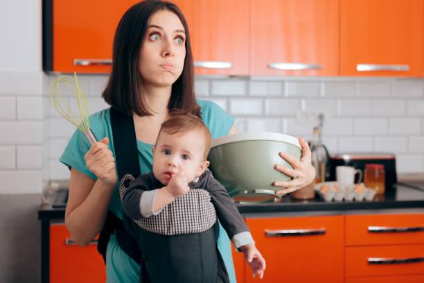 Beschäftigt Mom Kochen Holding Baby in Carrier Babywearing System – Foto