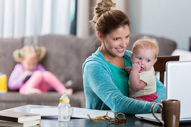 busy mom holds daughter while working - dona de casa - fotografias e filmes do acervo