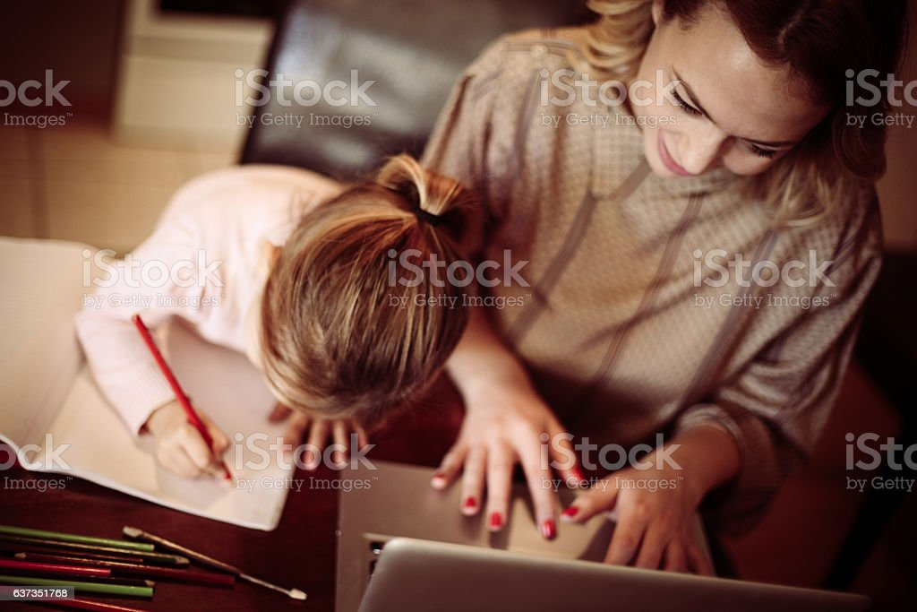 Busy mom. Above view of mother using laptop and her little daughter drawing at home. 4-5 Years Stock Photo