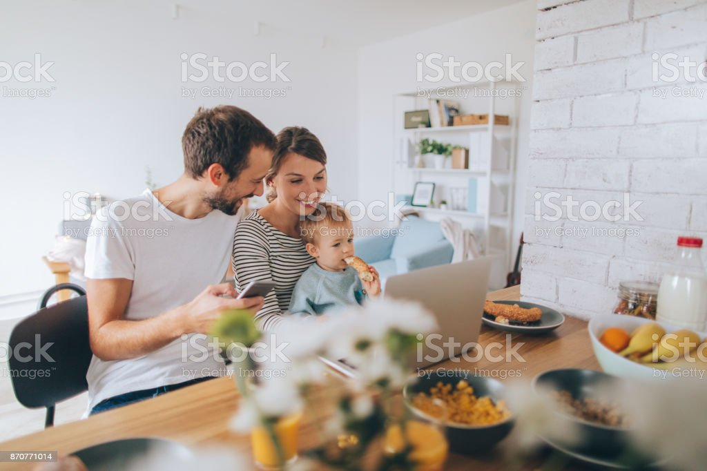 Busy mornings together Photo of a young family is showing their hectic lifestyle - busy morning they are spending together over dinning table, using computer and mobile phone while their toddler boy is with them 12-17 Months Stock Photo