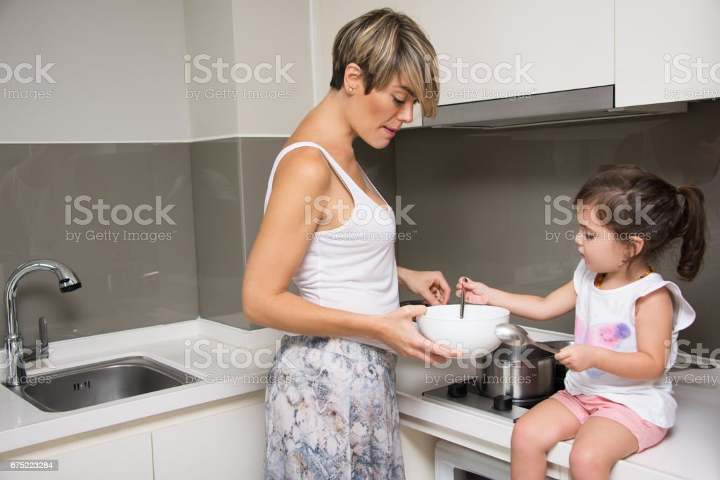 Busy mother and daughter cooking together royalty-free stock photo