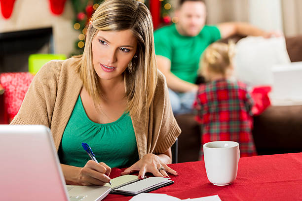 busy mother pays bills at christmastime - holiday and invoice family foto e immagini stock