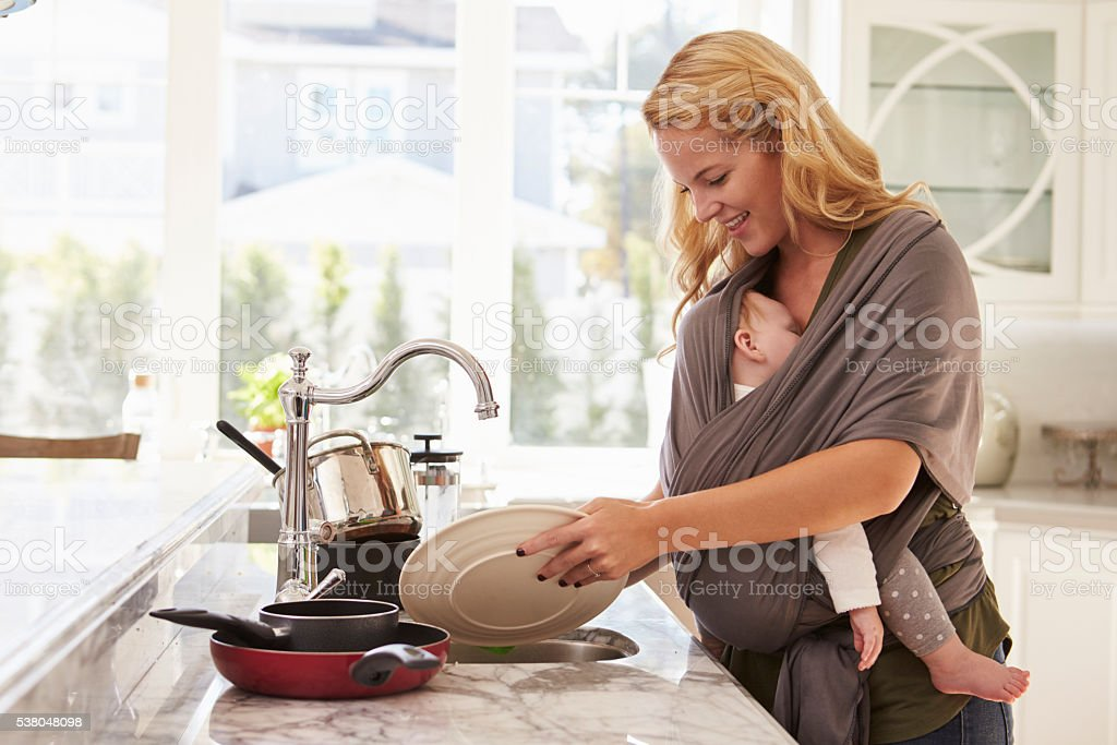 Busy Mother With Baby In Sling Multitasking At Home stock photo