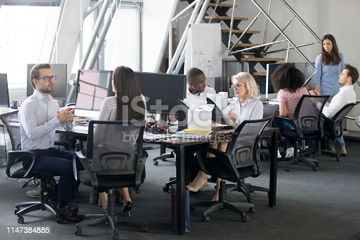 1090214584 istock photo Busy multi racial office employees working in coworking shared room 1147384885