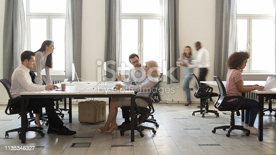 1090214584 istock photo Busy multicultural employees working on computers in modern office rush 1135346327