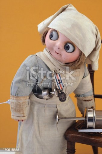 The doll is made from cloth, with a  composition mask face. Probably made in Germany in the early 20th century. Wearing a nurse costume with a medal. The  scene, including vintage medical equipment, is arranged by me.   Lightbox: