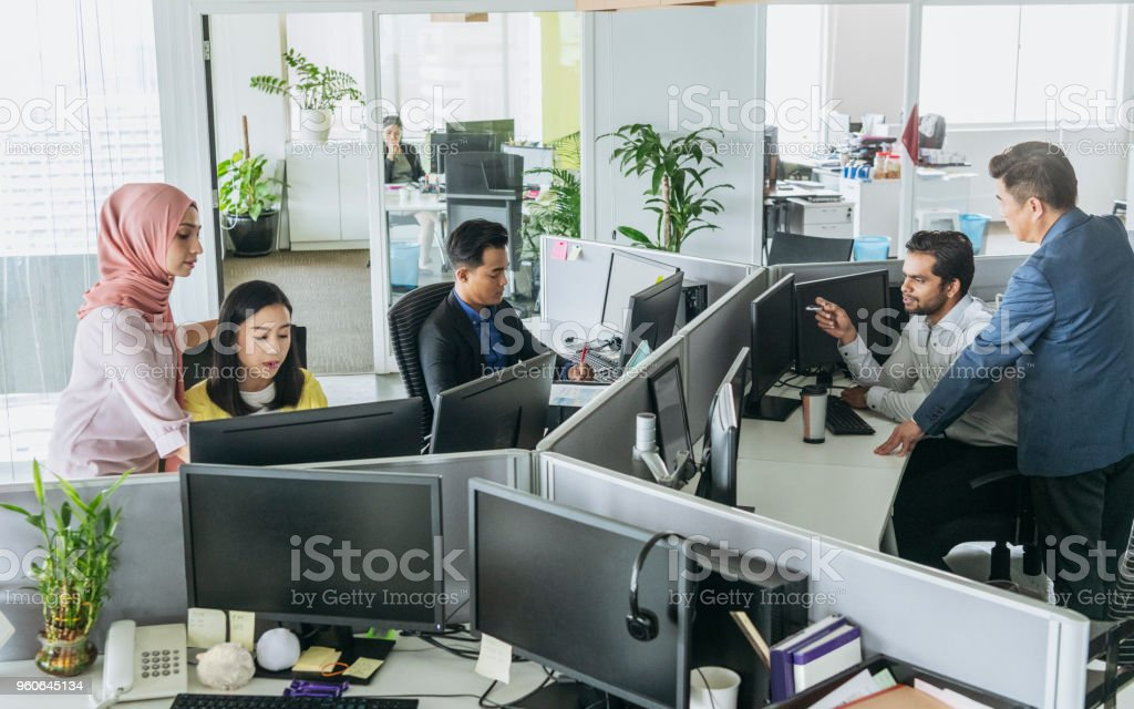 Busy office with men and women working at desks Multi racial businessmen and women using computers and discussing 20-29 Years Stock Photo