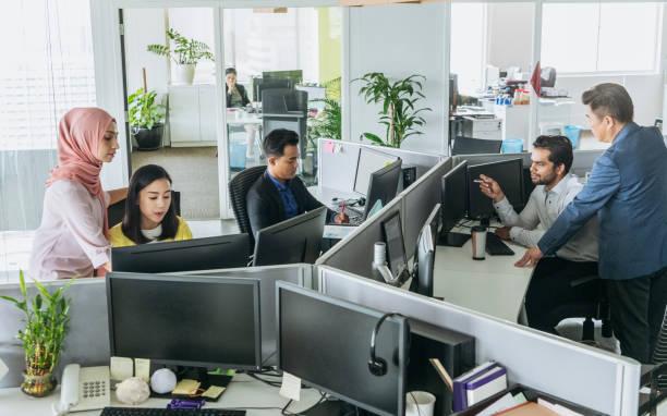 bureau occupé avec des hommes et des femmes qui travaillent aux guichets - business malaysia photos et images de collection