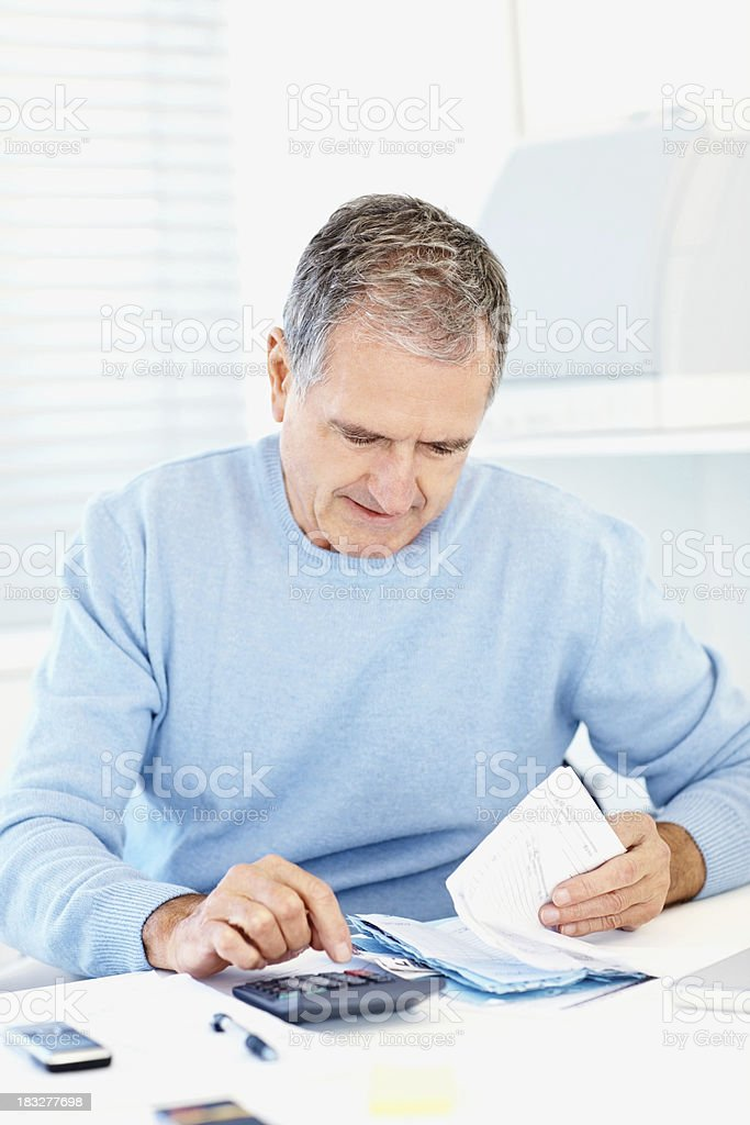 busy old man using calculator to pay monthly bills stock photo
