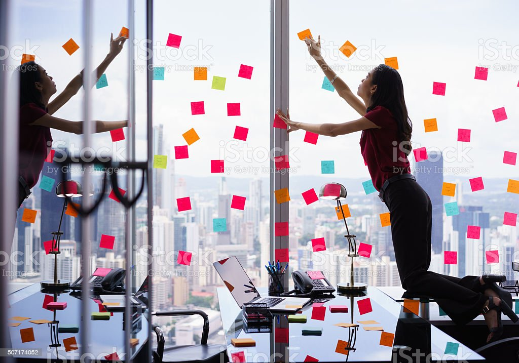 Busy Person Attaching Many Sticky Notes On Large Window stock photo