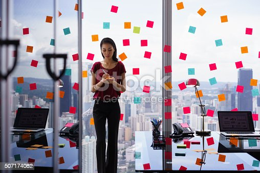 istock Busy Person Writing Many Sticky Notes On Large Window 507174082