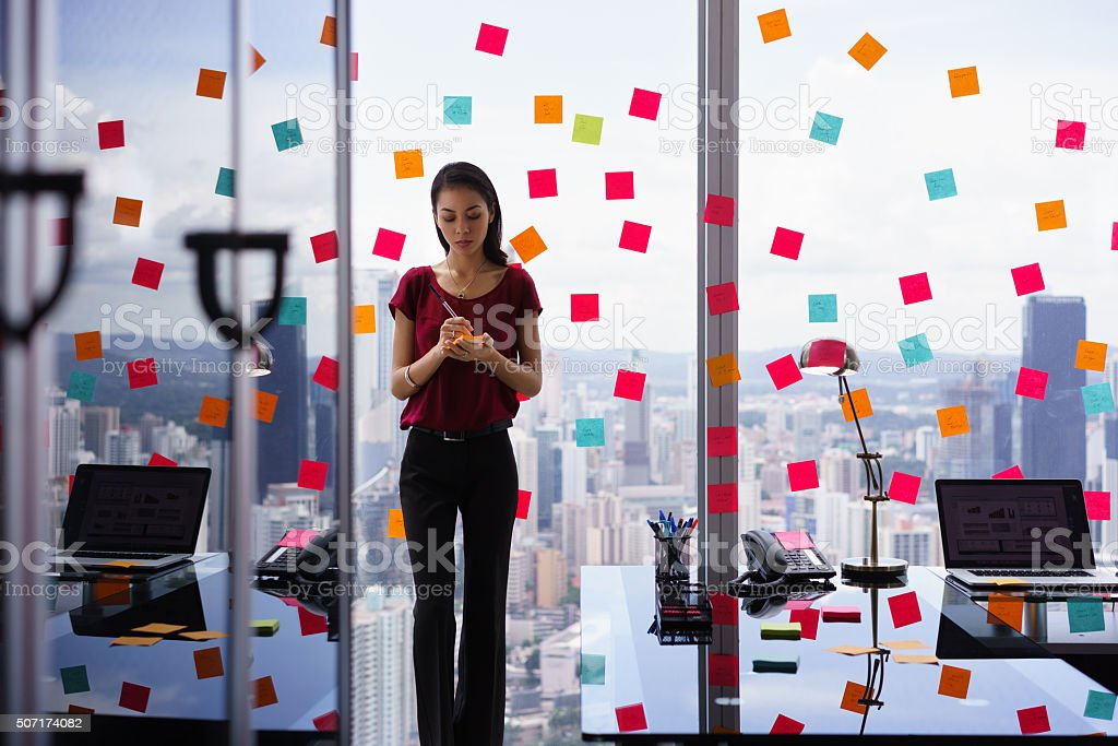 Busy Person Writing Many Sticky Notes On Large Window stock photo