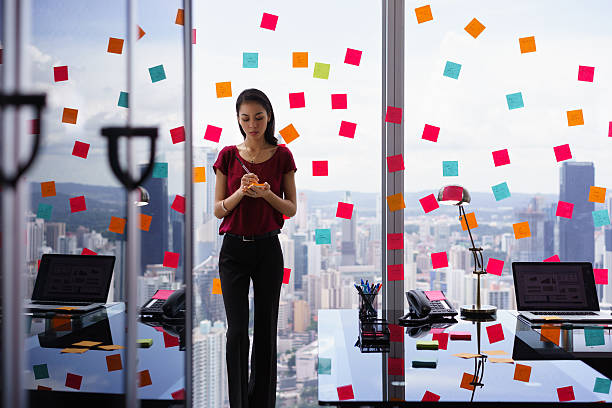 busy person writing many sticky notes on large window - modern lifestyle stock photos and pictures