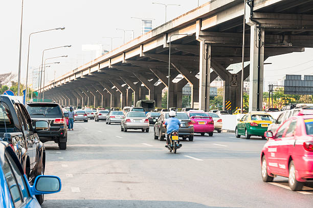 busy road and elevated highway bangkok, thailand - motorbike, umbrella stock pictures, royalty-free photos & images