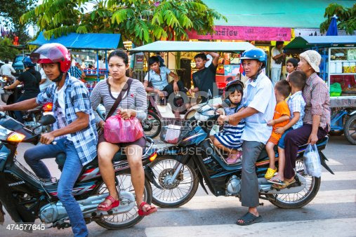 Siem Reap, Cambodia - November 27, 2012: Commuter and a Family riding a motorcycle. Busy road during rush hour.