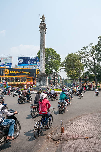 busy road junction in ho chi minh city, vietnam - motorbike, umbrella stock photos and pictures