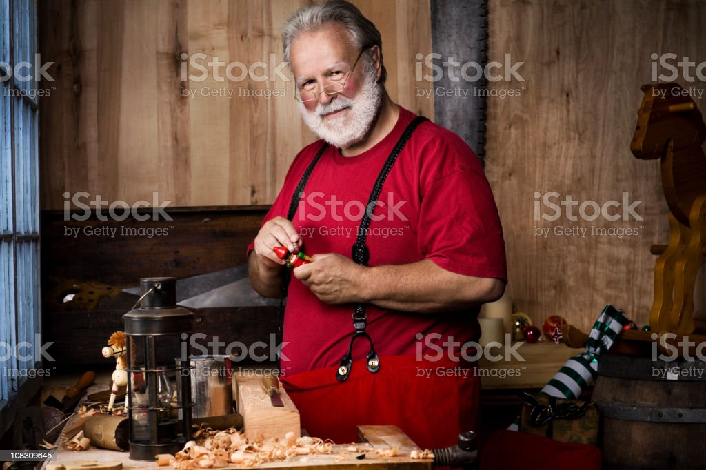 Busy Santa Claus Making Toys in Christmas Workshop, Copy Space stock photo