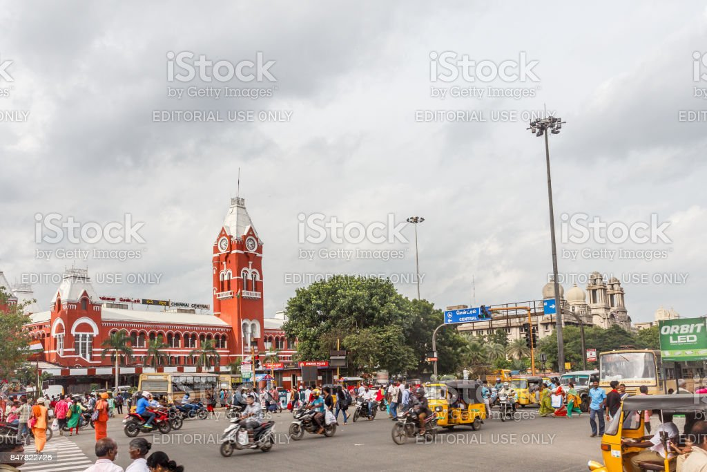 Busy scene in front of famous ancient railway station,vehicles pass by traffic signal,people are waiting to cross the road with dark clouds in the sky,Central railway station,Chennai,India,25 aug 2017 stock photo