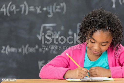 Confident African American schoolgirl works on math homework. She is sitting in front of a chalkboard.