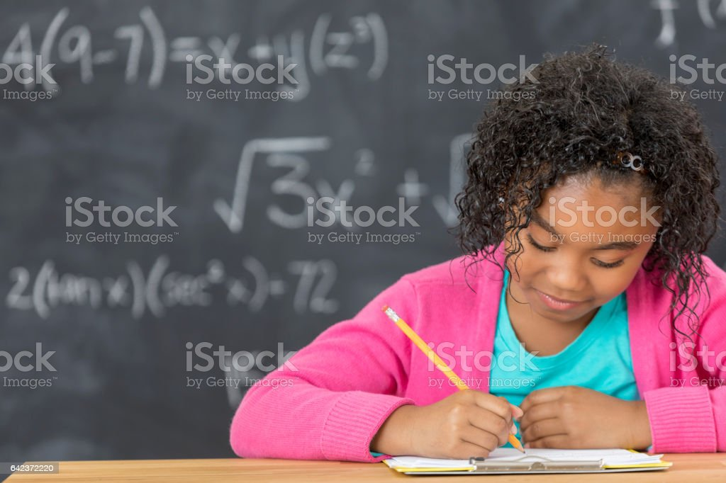 Busy schoolgirl works on assignment in front of chalkboard stock photo