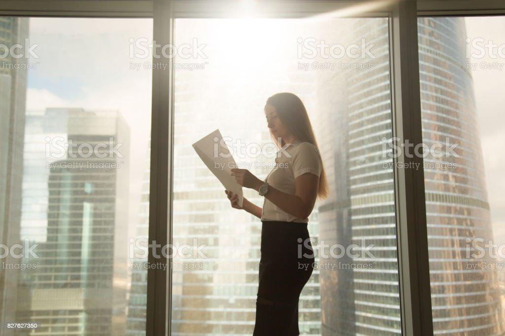 Voll ernst Geschäftsfrau hält Lesung Dokument, Stand in der Nähe großer Fenster – Foto