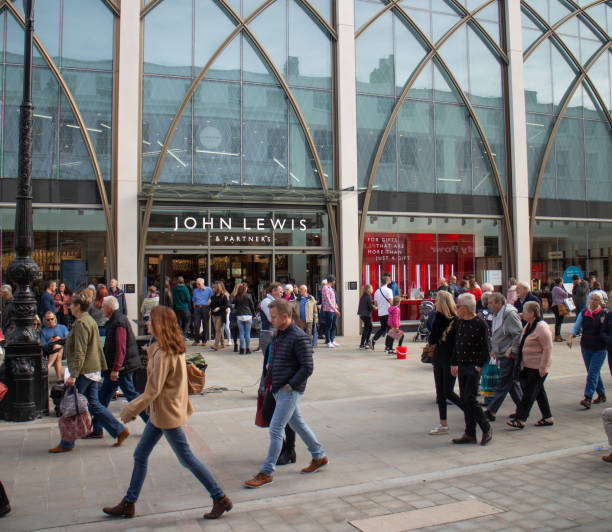 busy shoppers in the centre of cheltenham , in the cotswolds, walking past the newly opened john lewis & partners store - john lewis стоковые фото и изображения