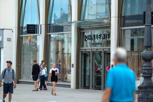 在科茨沃爾德的切爾滕納姆中心,忙碌的購物者走過新開張的約翰·路易斯和合作夥伴商店。 - john lewis 個照片及圖片檔