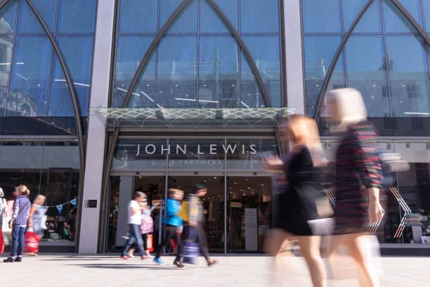 在科茨沃爾德的切爾滕納姆中心忙碌的購物者,走過高街的新約翰·路易斯和合作夥伴商店 - john lewis 個照片及圖片檔