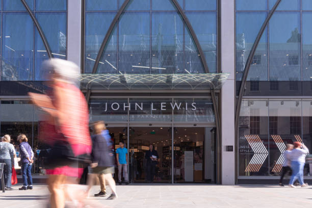 busy shoppers in the centre of cheltenham in the cotswolds, walking past the new john lewis & partners store in the high street - john lewis стоковые фото и изображения