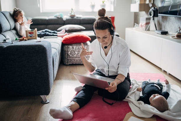 Busy single mother working at home and babysitting stock photo