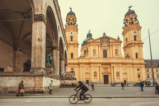 Busy square Odeonsplatz with bicyclists and pedestrians near historical structures