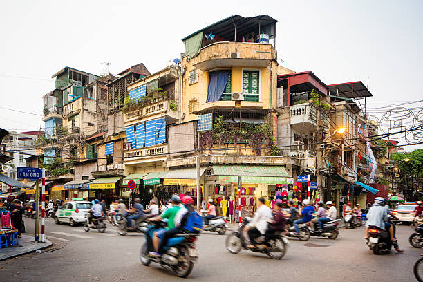 Busy street corner in old town Hanoi Vietnam Busy street corner in old town Hanoi, Vietnam. Lots of people are commuting on motorbikes or cars. The street is lined by stores and appartment buildings. editorial stock pictures, royalty-free photos & images