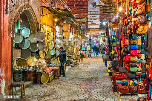 People are walking in one of narrow streets in the souk of Marrakech, Morocco.