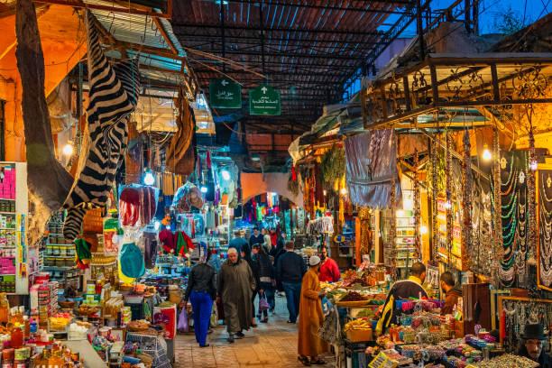 drukke straat in de souks van marrakech, marokko - bazaar stockfoto's en -beelden