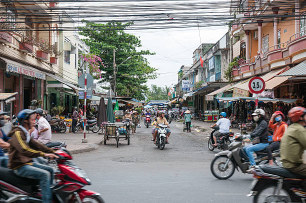 busy street scene at my tho in vietnam - motorbike, umbrella stock pictures, royalty-free photos & images