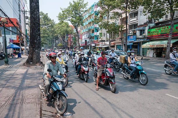 busy street scene in ho chi minh city, vietnam - motorbike, umbrella stock pictures, royalty-free photos & images